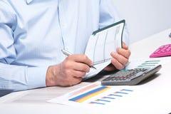 Επιχειρηματίας με το σημειωματάριο στο γραφείο Στοκ εικόνες με δικαίωμα ελεύθερης χρήσης