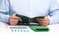 Επιχειρηματίας με το σημειωματάριο στο γραφείο Στοκ Φωτογραφία