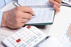 Επιχειρηματίας με το σημειωματάριο στο γραφείο Στοκ Εικόνες