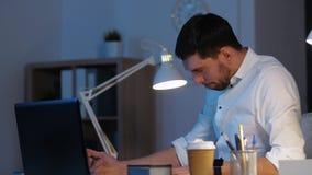 Επιχειρηματίας με το σχεδιάγραμμα και το lap-top τη νύχτα απόθεμα βίντεο