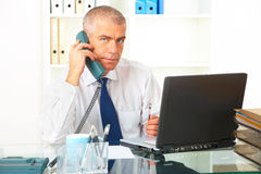 Επιχειρηματίας με το τηλέφωνο και το lap-top Στοκ φωτογραφία με δικαίωμα ελεύθερης χρήσης