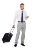 Επιχειρηματίας με το τηλέφωνο και βαλίτσα που εξετάζει τη κάμερα Στοκ Εικόνες