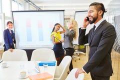 Επιχειρηματίας με το τηλέφωνο κυττάρων στη συνεδρίαση Στοκ εικόνες με δικαίωμα ελεύθερης χρήσης