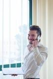 Επιχειρηματίας με το τηλέφωνο μπροστά από το παράθυρο Στοκ Εικόνα