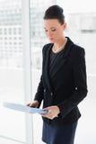 Επιχειρηματίας με το φάκελλο που στέκεται ενάντια στον τοίχο γυαλιού γραφείων Στοκ Φωτογραφία