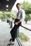 Επιχειρηματίας με το φάκελλο που στέκεται και που χρησιμοποιεί το smartphone υπαίθρια Στοκ φωτογραφία με δικαίωμα ελεύθερης χρήσης