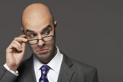 Επιχειρηματίας με το χέρι στα γυαλιά που κάνει ένα πρόσωπο Στοκ Φωτογραφίες