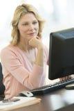 Επιχειρηματίας με το χέρι στο πηγούνι που εξετάζει τον υπολογιστή στην αρχή Στοκ εικόνες με δικαίωμα ελεύθερης χρήσης