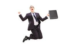Επιχειρηματίας με το χαρτοφύλακα που πηδά από τη χαρά στοκ φωτογραφία