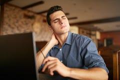 Επιχειρηματίας με το backpain μετά από τις πολλές ώρες στην εργασία που τρίβει το λαιμό του λόγω του πόνου Καταπονημένο όμορφο άτ Στοκ Εικόνες