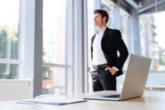Επιχειρηματίας με το lap-top και έγγραφα που στέκονται κοντά στο παράθυρο Στοκ εικόνες με δικαίωμα ελεύθερης χρήσης