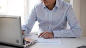 Επιχειρηματίας με το lap-top και έγγραφα στο γραφείο φιλμ μικρού μήκους