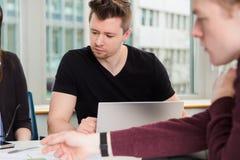 Επιχειρηματίας με το lap-top και συνάδελφοι που κάθονται στο γραφείο Στοκ Εικόνες