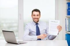 Επιχειρηματίας με το lap-top και σύμβαση στο γραφείο Στοκ φωτογραφία με δικαίωμα ελεύθερης χρήσης