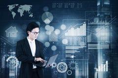 Επιχειρηματίας με το lap-top και την οικονομική στατιστική Στοκ Εικόνες