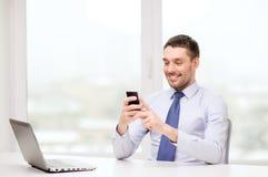 Επιχειρηματίας με το lap-top και smartphone στο γραφείο Στοκ φωτογραφία με δικαίωμα ελεύθερης χρήσης