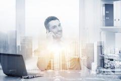 Επιχειρηματίας με το lap-top και smartphone στο γραφείο Στοκ Φωτογραφία