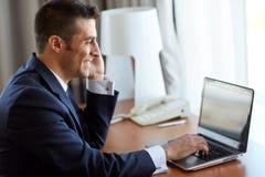 Επιχειρηματίας με το lap-top και smartphone στο ξενοδοχείο Στοκ Φωτογραφία