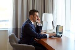 Επιχειρηματίας με το lap-top και smartphone στο ξενοδοχείο Στοκ Εικόνα
