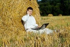 Επιχειρηματίας με το lap-top κοντά στις θυμωνιές χόρτου Στοκ εικόνες με δικαίωμα ελεύθερης χρήσης