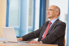 Επιχειρηματίας με το lap-top που εξετάζει επάνω το γραφείο γραφείων Στοκ εικόνες με δικαίωμα ελεύθερης χρήσης