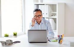 Επιχειρηματίας με το lap-top που καλεί το smartphone Στοκ φωτογραφία με δικαίωμα ελεύθερης χρήσης