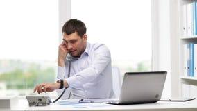 0 επιχειρηματίας με το lap-top που καλεί το τηλέφωνο φιλμ μικρού μήκους