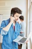 Επιχειρηματίας με το lap-top που καλεί το τηλέφωνο Στοκ εικόνα με δικαίωμα ελεύθερης χρήσης