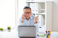 Επιχειρηματίας με το lap-top που καλεί το smartphone Στοκ Φωτογραφίες