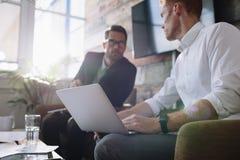 Επιχειρηματίας με το lap-top που μιλά με το συνάδελφο κατά τη διάρκεια της συνεδρίασης Στοκ φωτογραφία με δικαίωμα ελεύθερης χρήσης