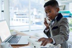 Επιχειρηματίας με το lap-top που χρησιμοποιεί το τηλέφωνο στο γραφείο Στοκ Εικόνες