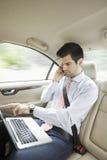 Επιχειρηματίας με το lap-top στο αυτοκίνητό του Στοκ Φωτογραφία