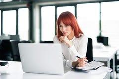 Επιχειρηματίας με το lap-top στο γραφείο της στο γραφείο, εργασία Στοκ Φωτογραφία