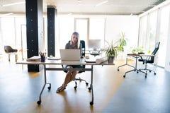 Επιχειρηματίας με το lap-top στο γραφείο της στο γραφείο, εργασία Στοκ φωτογραφία με δικαίωμα ελεύθερης χρήσης