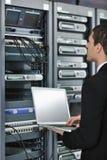 Επιχειρηματίας με το lap-top στο δωμάτιο κεντρικών υπολογιστών δικτύων Στοκ Εικόνες