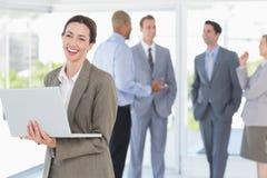 Επιχειρηματίας με το lap-top του και οι συνάδελφοί της πίσω Στοκ Φωτογραφία