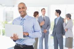 Επιχειρηματίας με το lap-top του και οι συνάδελφοί του πίσω Στοκ φωτογραφία με δικαίωμα ελεύθερης χρήσης
