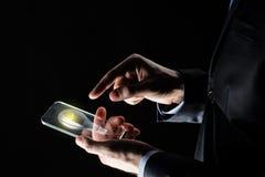 Επιχειρηματίας με το lightbulb στο smartphone Στοκ Εικόνες