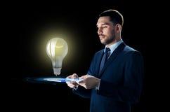 Επιχειρηματίας με το PC ταμπλετών και lightbulb Στοκ εικόνα με δικαίωμα ελεύθερης χρήσης