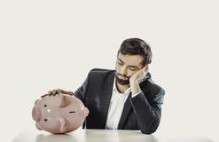 Επιχειρηματίας με το piggybank από ένα γραφείο στοκ φωτογραφία