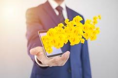 Επιχειρηματίας με το smartphone με τα σύμβολα δολαρίων που βγαίνουν από την οθόνη Στοκ Εικόνες