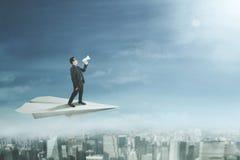 Επιχειρηματίας με megaphone στο αεροπλάνο εγγράφου Στοκ εικόνα με δικαίωμα ελεύθερης χρήσης