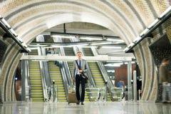 Επιχειρηματίας μπροστά από τις κυλιόμενες σκάλες σε έναν σταθμό μετρό Στοκ εικόνα με δικαίωμα ελεύθερης χρήσης