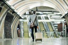 Επιχειρηματίας μπροστά από τις κυλιόμενες σκάλες σε έναν σταθμό μετρό Στοκ Φωτογραφία