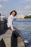 Επιχειρηματίας νέων κοριτσιών που στηρίζεται μετά από μια ημέρα στην όχθη ποταμού Στοκ Φωτογραφία