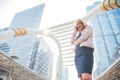 Επιχειρηματίας ομορφιάς που χρησιμοποιεί το κινητό τηλέφωνο για την επικοινωνία με τους πελάτες στην πόλη r Μητρόπολη στοκ εικόνες