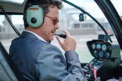 Επιχειρηματίας πίσω από το τιμόνι του ελικοπτέρου του στοκ εικόνα