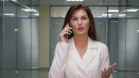 Επιχειρηματίας πιπεροριζών που μιλά στο κινητό τηλέφωνο στο διάδρομο του γραφείου απόθεμα βίντεο