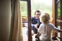 Επιχειρηματίας που έρχεται κατ' οίκον, λίγος γιος που τρέχει στα όπλα του Στοκ Φωτογραφίες
