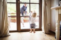 Επιχειρηματίας που έρχεται κατ' οίκον, λίγος γιος στην πόρτα που καλωσορίζει τον Στοκ φωτογραφίες με δικαίωμα ελεύθερης χρήσης